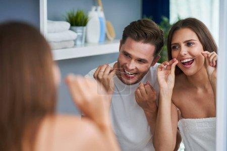 Photo pour Joyeux jeune couple soie dentaire dans la salle de bain - image libre de droit