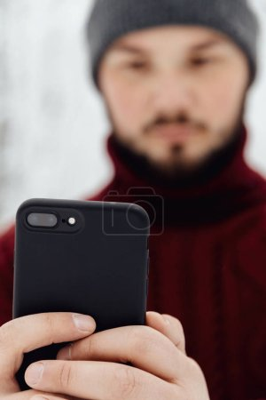 Photo for Guy in a red knitted sweater and jeans holding a phone, standing on the snow in the winter forest - Royalty Free Image