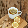 Cup of ginger tea with lemon on old wooden table, ...