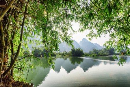 Blick auf den Yulong-Fluss und schöne Karstberge durch grünes Laub des Baumes. malerische Hügel, die sich im Wasser spiegeln. atemberaubende Landschaft bei Yangshuo County von Guilin, China.