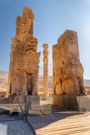 Photo pour Ruines panoramiques de la Porte de tous les Peuples sur fond de ciel bleu à Persépolis, Iran. Ancienne ville persane. Persépolis est une destination touristique populaire du Moyen-Orient . - image libre de droit