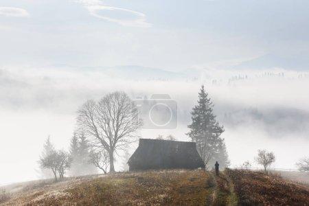 Photo pour Vallée de montagne pendant le lever du soleil. Maison seule sur automne brumeux pré. Carpates, photographie de paysage - image libre de droit
