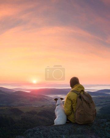 Photo pour Seul touriste assis sur le bord de la falaise avec chien dans le contexte d'un paysage de montagne incroyable. Journée ensoleillée et ciel bleu - image libre de droit