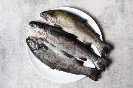 Three trout fish on white plate