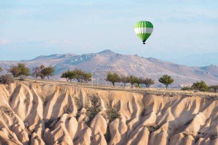 Photo pour Ballon vert dans le ciel du lever du soleil. Cappadoce, Turquie. Photographie de paysage - image libre de droit