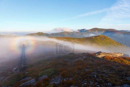 Photo pour Illusion d'optique Brocken Spectre dans la prairie parmi les plus hautes montagnes du matin brouillard et ciel bleu . - image libre de droit