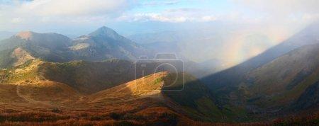 Photo pour De la pelouse avec de l'herbe orange ouvre un panorama de hautes montagnes, ciel bleu avec des nuages et un Brocken Spectre dans le brouillard un jour d'automne . - image libre de droit