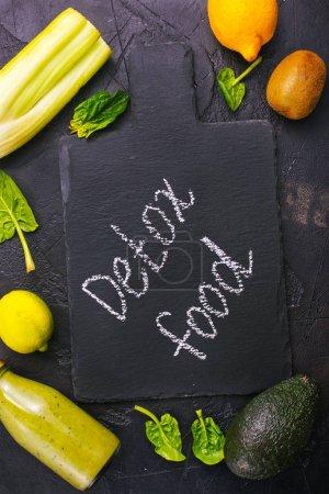 detox food inscription on blackboard, smoothie in bottle and ingredients