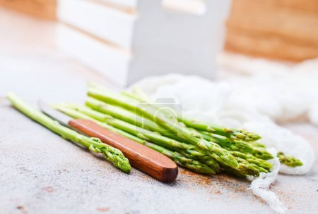 fresh green asparagus and knife on table, diet food