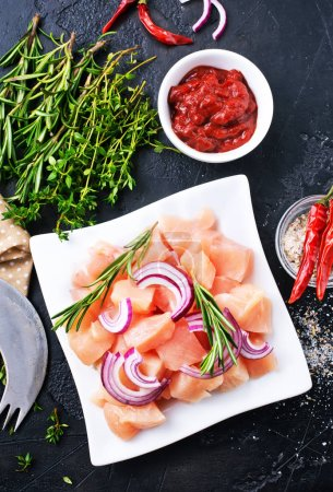 sliced raw chicken breast and different ingredients for cooking