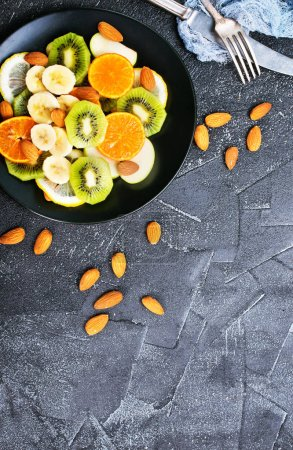 fruit salad with almonds on black plate
