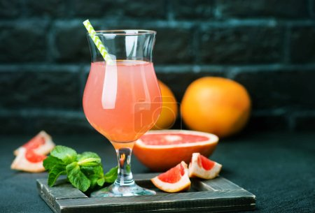 Photo for Grapefruit juice in glass and on a table - Royalty Free Image