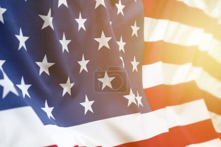 Closeup of rippled American flag. Sunlight shining from end of