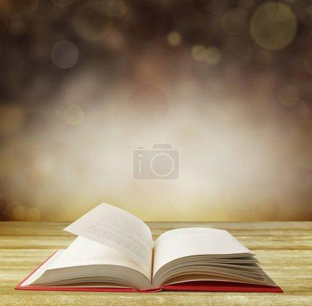 Photo pour Livre ouvert sur table devant fond abstrait - image libre de droit