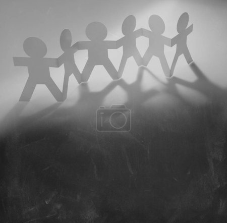 Photo for Team of paper chain people in a row holding hands - Royalty Free Image