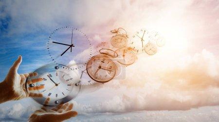 Photo pour Mains et horloges dans le ciel - image libre de droit