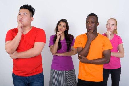 Photo pour Studio shot de divers groupes d'amis multiethniques pensant tout en levant les yeux ensemble - image libre de droit