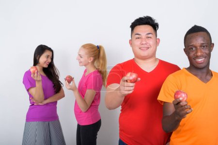 Photo for Happy diverse group of multi ethnic friends smiling while holding red apple together with friends talking in the back - Royalty Free Image