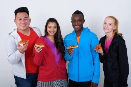 Foto de Captura de estudio de feliz grupo diverso de amigos multiétnicos sonriendo mientras sostienen rebanada de pizza juntos - Imagen libre de derechos
