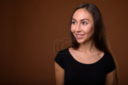 Photo for Studio shot of young beautiful woman wearing black shirt against brown background - Royalty Free Image