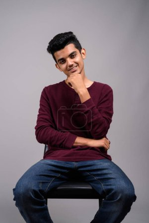 Young Indian man against gray background