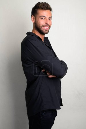 Photo for Studio shot of young handsome bearded businessman against white background - Royalty Free Image