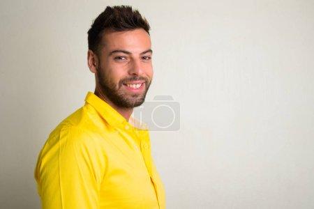 Foto de Disparo de estudio del joven empresario barbudo guapo con camiseta amarillo sobre fondo blanco - Imagen libre de derechos