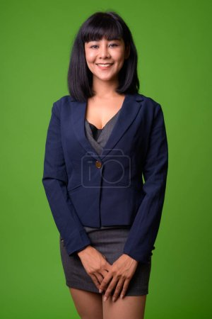 Photo pour Studio shot de jeune belle femme d'affaires asiatique sur fond vert - image libre de droit