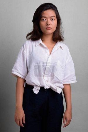 Photo pour Photo de Studio de belle jeune femme asiatique avec les cheveux courts sur fond blanc - image libre de droit
