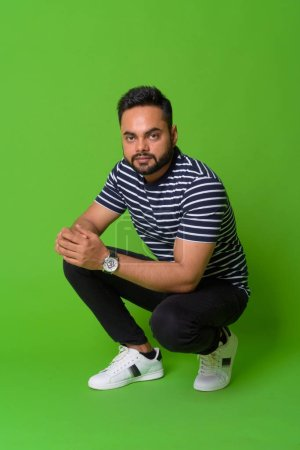 Photo for Studio shot of young bearded Indian man against chroma key with green background - Royalty Free Image
