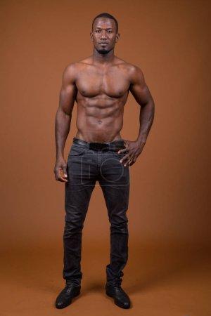 Photo pour Photo de Studio de bel homme africain musclé torse nu sur fond brun - image libre de droit