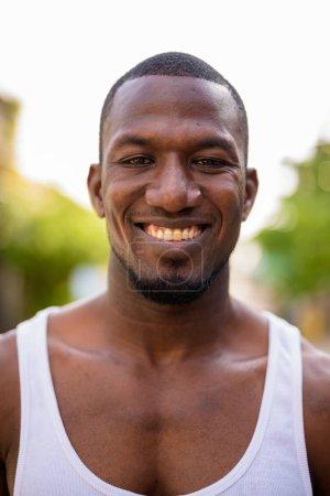 Photo pour Portrait de bel homme africain musclé vêtu d'un débardeur dans les rues à l'extérieur - image libre de droit