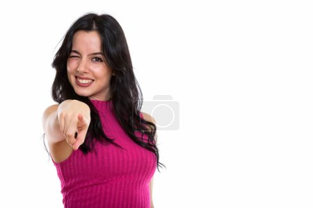 Studio shot of young happy Spanish woman smiling while pointing
