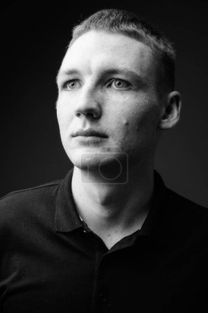 Photo for Studio shot of young man against black background in black and white - Royalty Free Image