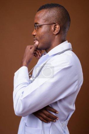 Photo pour Prise de vue en studio d'un jeune médecin africain portant des lunettes sur fond brun - image libre de droit