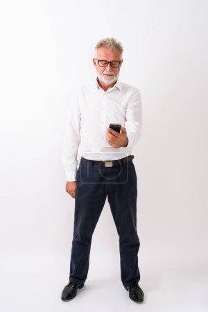 Photo pour Coup de corps plein de beau senior homme barbu debout GSM sur fond blanc - image libre de droit