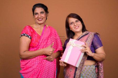 Photo pour Plan studio de deux femmes indiennes matures portant ensemble des vêtements traditionnels indiens Sari sur fond marron - image libre de droit