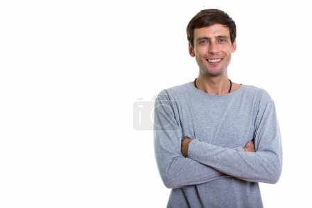 Photo for Studio shot of happy young handsome man smiling with arms crossed - Royalty Free Image