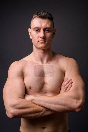 Photo for Studio shot of young handsome man shirtless against gray background - Royalty Free Image