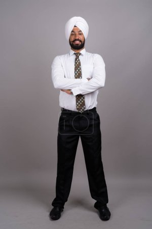 Joven hombre de negocios sikh indio guapo usando turbante contra gr