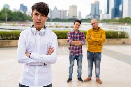Photo pour Portrait de trois jeunes hommes asiatiques se relaxant ensemble au parc à Bangkok, Thaïlande - image libre de droit