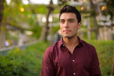 Photo pour Portrait de jeune homme d'affaires hispanique beau obtenir de l'air frais avec la nature dans la ville en plein air - image libre de droit