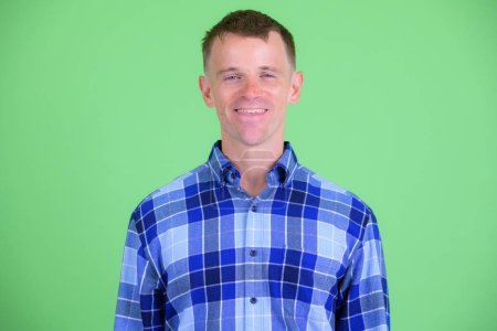 Photo for Studio shot of hipster man wearing blue checkered shirt against green background - Royalty Free Image