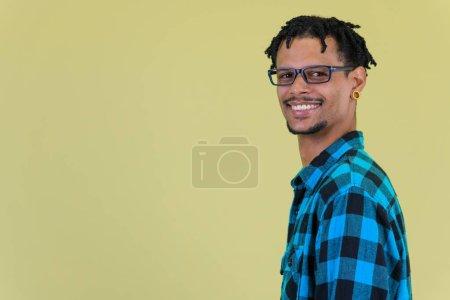 Photo pour Studio shot de jeune homme hipster africain beau avec dreadlocks sur fond coloré - image libre de droit