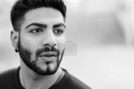 Photo pour Portrait de jeune homme indien beau avec barbe en plein air tourné en noir et blanc - image libre de droit