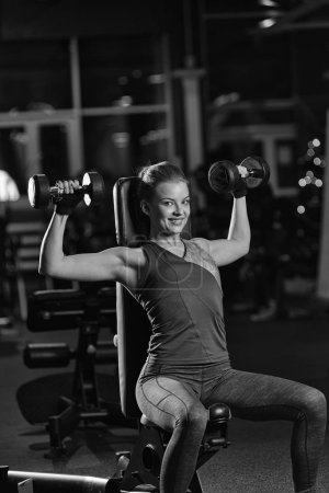 Photo for Beautiful sporty woman doing power fitness exercise at sport gym. Girl with dumbbell. Black and white. - Royalty Free Image