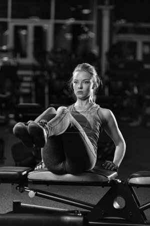 Photo for Woman doing strength exercises for abdominal muscles at indoor sport gym. Girl doing yoga stretches after running. Fitness model in dark sport club. Black and white. - Royalty Free Image