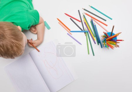 Little kid drawing with colour pencils