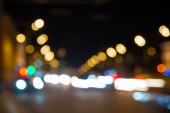 Nights lights of the big city, the night avenue with road markings and headlights of the approaching cars.