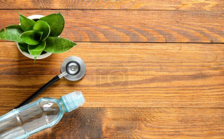 stethoscope, water and flowerpot on wood background